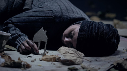 Freezing refugee sleeping on street and holding paper house, missing home