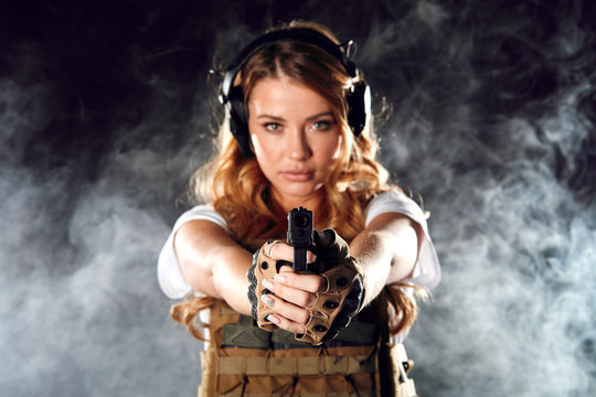 Armed beautiful blonde woman wearing protective headphones and plate carrier, shoots with gun at a target in the darkness with smoke clouds