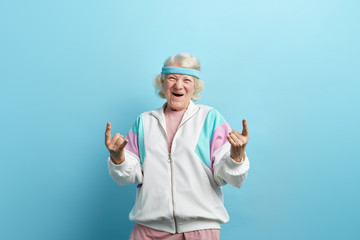 Cute hipster grandmother smiling and making rock sign against blue studio background