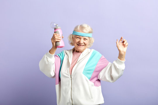 Dancing retired woman with gray hair tied above headband smiling satisfied, holding a shaker with water, remembering that hydration is important for the body.