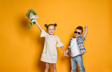 Image of young happy caucasian boy gives a flowers to his girlfriend isolated over yellow background.