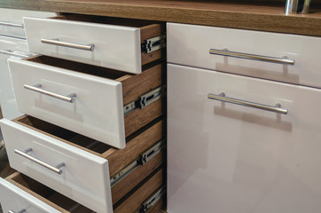 Fototapeta Wooden furniture with drawers and glossy white MDF facades obraz