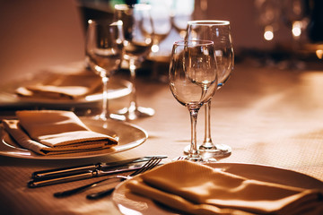 served table with white tablecloth. white plates, wine glass, fork, knife