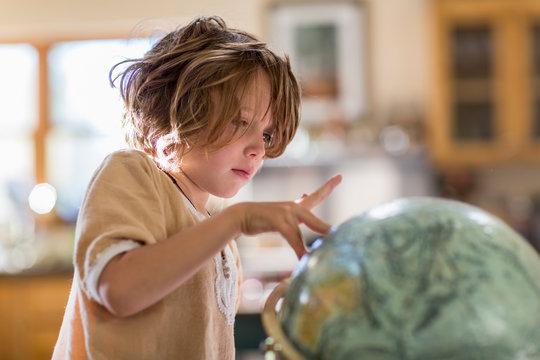 5 year old boy touching globe