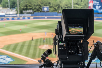Broadcast television camera shooting a baseball game on a sunny day
