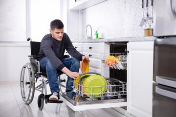 Handicapped Man Arranging Plates In Dishwasher