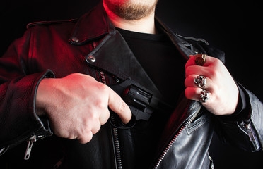 Biker in leather jacket pulling out revolver.