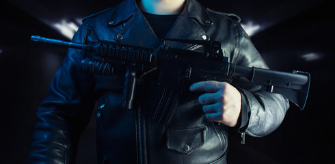 Biker in leather jacket holding rifle.