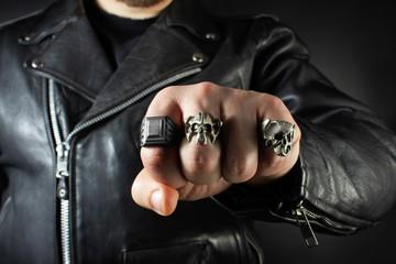 Biker man in leather jacket showing fist.