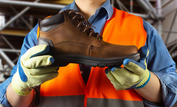 Worker in orange jacket outfit holding boot.
