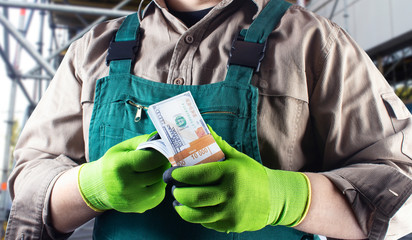 Worker in green overall outfit with dollars.