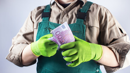 Worker in green overall outfit with euro banknotes.