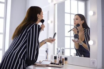 Attractive young woman doing make-up while looking at the mirror and smiling