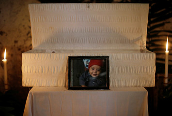 A picture is seen beside casket of the body of 2-1/2-year-old Guatemalan migrant Wilmer Josue Ramirez, during his wake in the village of Olopa