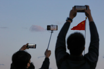 People take pictures of the lowering ceremony of the Chinese national flag that is held daily at sunset in Tiananmen Square in Beijing