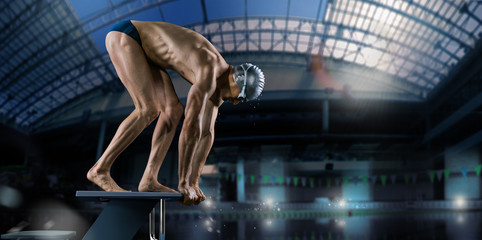 Swimming pool. Muscular swimmer ready to jump. Wall mural