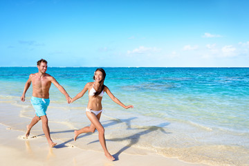Wall Mural - Beach vacation couple running of joy relaxing on tropical summer travel destination paradise - honeymoon holidays. Man and woman in swimwear holding hands happy.