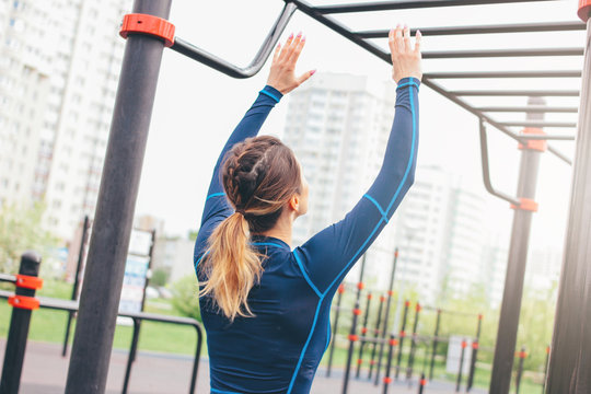 Attractive fit young woman in sport wear girl pulls up on the bar at street workout area. The healthy lifestyle in city