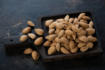 Black wooden serving tray with unpeeled almond nuts, studio shot over dark brown stone surface