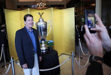 U.S. Ambassador to Japan Hagerty takes a picture with The President's Cup, which U.S. President Trump will present to the winner of a sumo wrestling tournament, is on display at the Palace Hotel in Tokyo