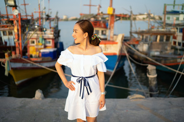 portrait Young woman in a white dress posing on the outdoor sunset light with blur boat Travel and Vacation. Freedom and relax Concept.