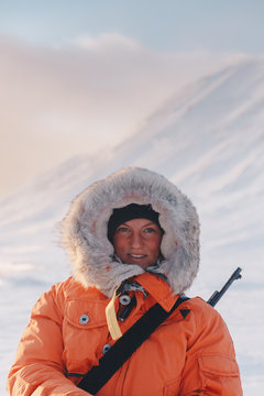 young female hunter wearing an orange jacket with fur and behind there is winter landscape in sunset