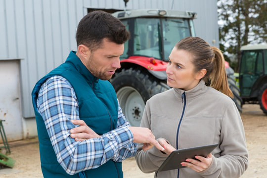 man and woman on farm looking at digital tablet