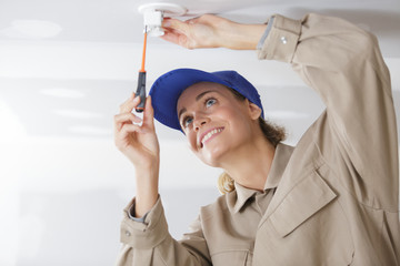 woman installing light fitting