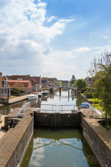 A canal with lock in a historical city in the lake side district of the Netherlands.