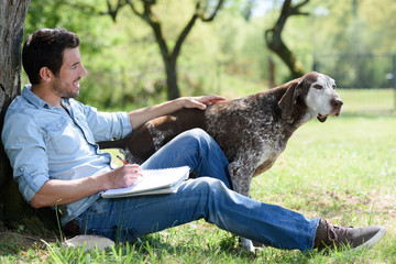 man sat by tree sketching with his dog