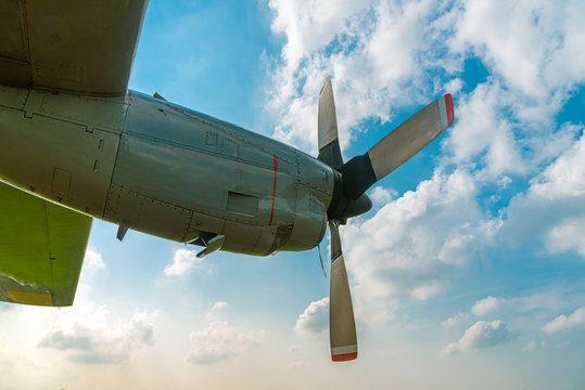 Aircraft Propeller and Spinner Engine on Airplane Wing Against Cloudy Blue Sky. Four Blade Aircraft Propeller