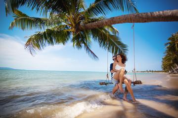 Couple on swing on tropical beach