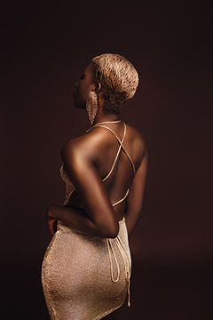 back view of young glamorous african american woman with short hair isolated on brown