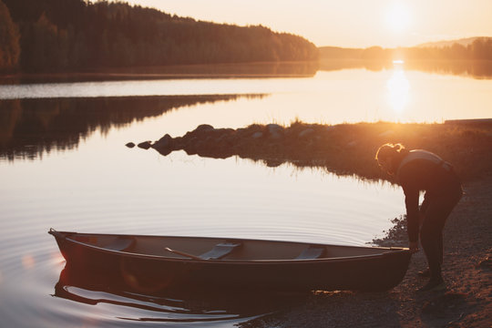 young man puts a canoe boat in the water at sunset with a beautiful landscape in the background.