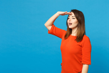 Beautiful young woman wearing orange dress holding hand at forehead looking far away distance isolated over blue wall background, studio portrait. People lifestyle fashion concept. Mock up copy space.