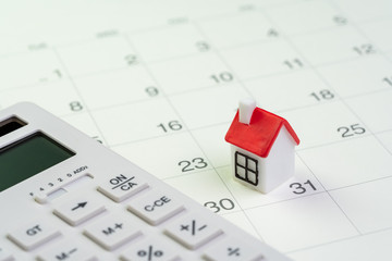 House mortgage payment and installment schedule concept, small miniature house on end of month calendar with calculator