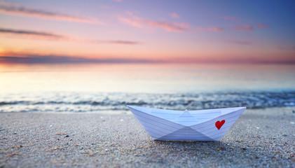 kleines Papierboot am Strand
