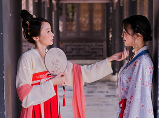 Two young women wearing in Chinese Han clothing in traditional Chinese buildings.