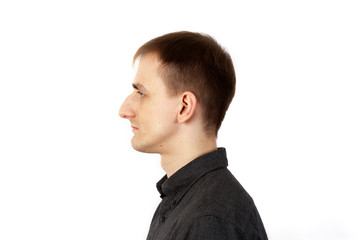 Tall thin young man stands on white background in profile Wall mural