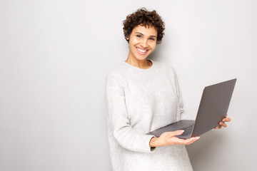 smiling young woman holding laptop computer by white background