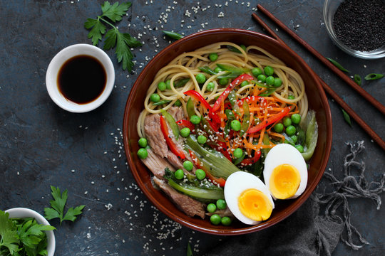 Noodles with beef, vegetables and eggs in bowl on dark background. Top view with copy space. Asian food.