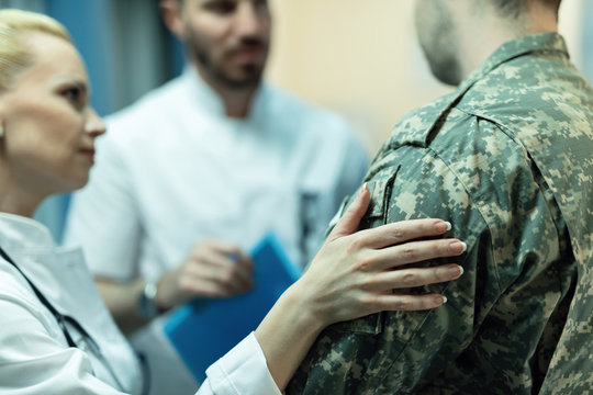 Close up of doctors consoling military officer in the hospital.