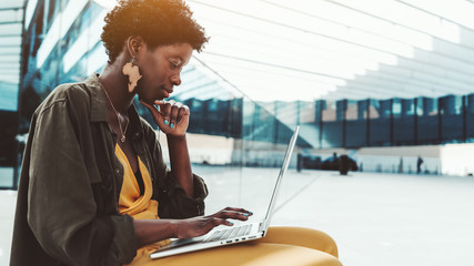 A pensive black female entrepreneur with curly Afro hair with the laptop on the bench in an outdoor area of her office building; young charming African woman with the netbook is answering to e-mail