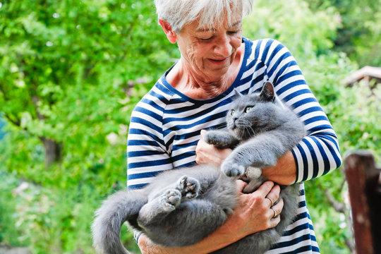 Frau schmust mit Katze auf dem Arm