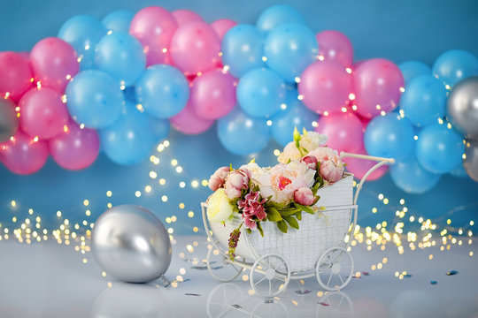Colorful decoration background with stroller, flowers and balloons for a first birthday party