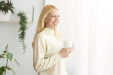 Happy Mature Woman Enjoying Morning Coffee At Home