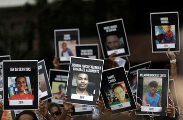 Residents from Rio's favelas show pictures of violence victims as they take part in a protest against violence near Ipanema beach in Rio de Janeiro