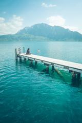 Kobieta samotnie siedzi  na pomoście nad górskim jeziorem w słoneczny dzień.
