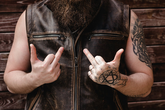 Strong brutal man with a beard and tattoos on his hands dressed in leather vest shows middle fingers