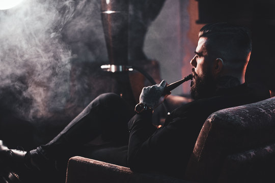 Groomed bearded man is relaxing on lounge near fireplace while smoking hookah. He has tattoo on his hand.